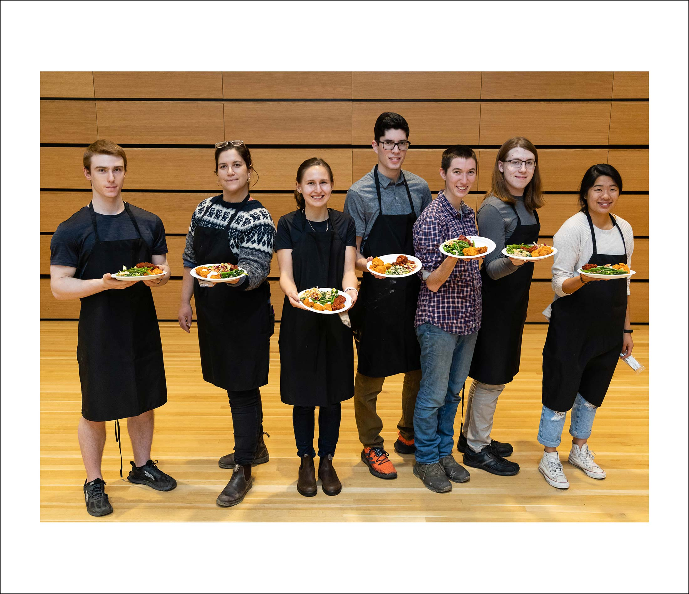 Seven people wearing black aprons, each holding a plateful of food