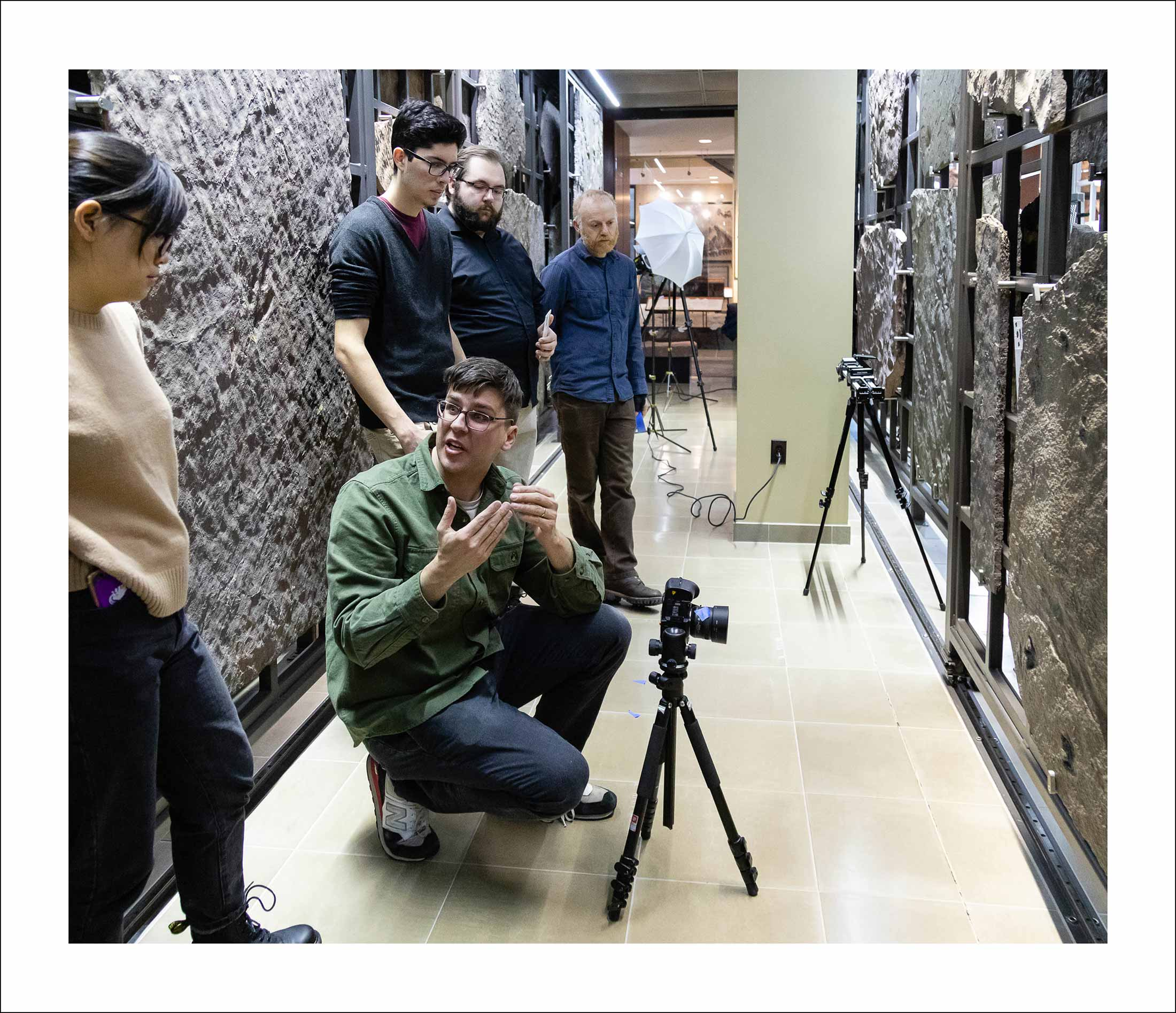 Four people in a hallway listen as a man talks, squatting in front of a camera on a tripod.