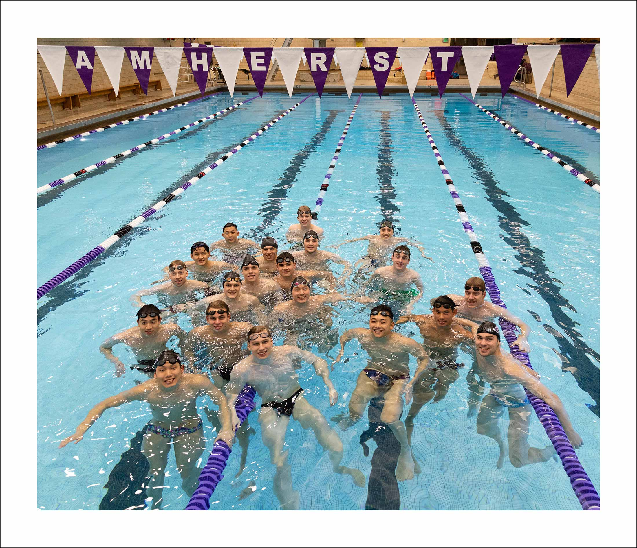 A large group of men smiling at the camera from inside of a swimming pool