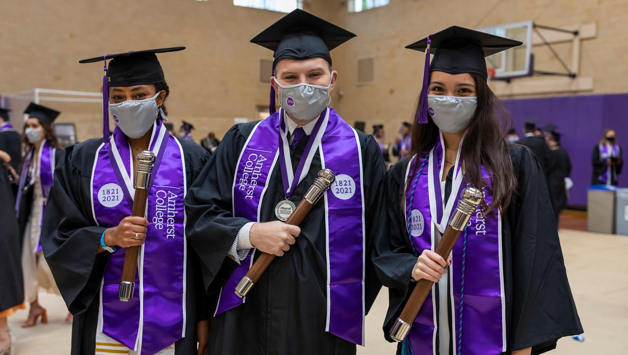 three seniors hold batons as they prepare to lead the Class of 2021 commencement procession