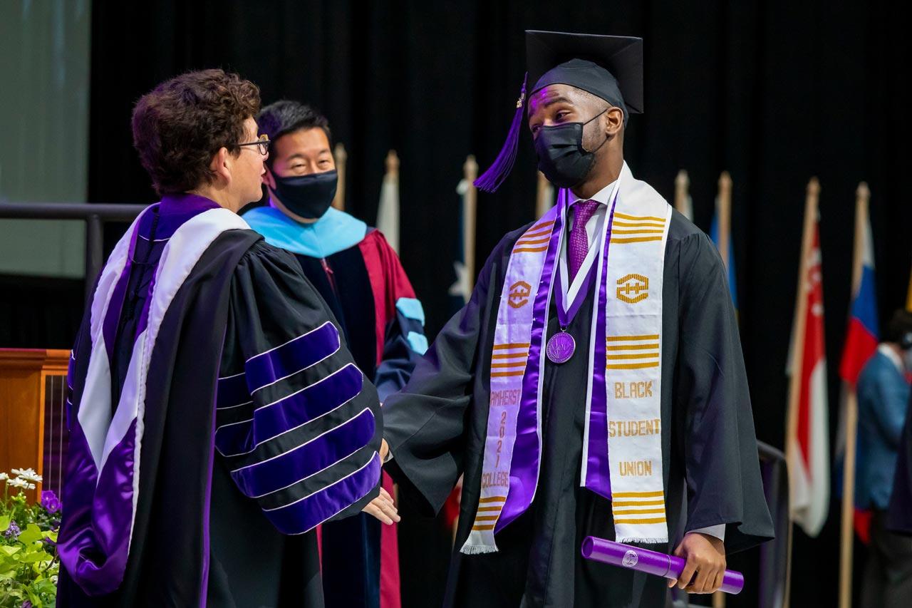 Rhodes Scholar Jeremy Thomas 21 receives his diploma from President Biddy Martin