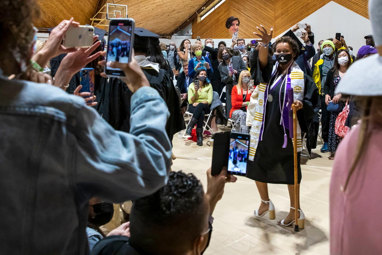 After the ceremony, Ayodele Lewis 21 waves as her father films her