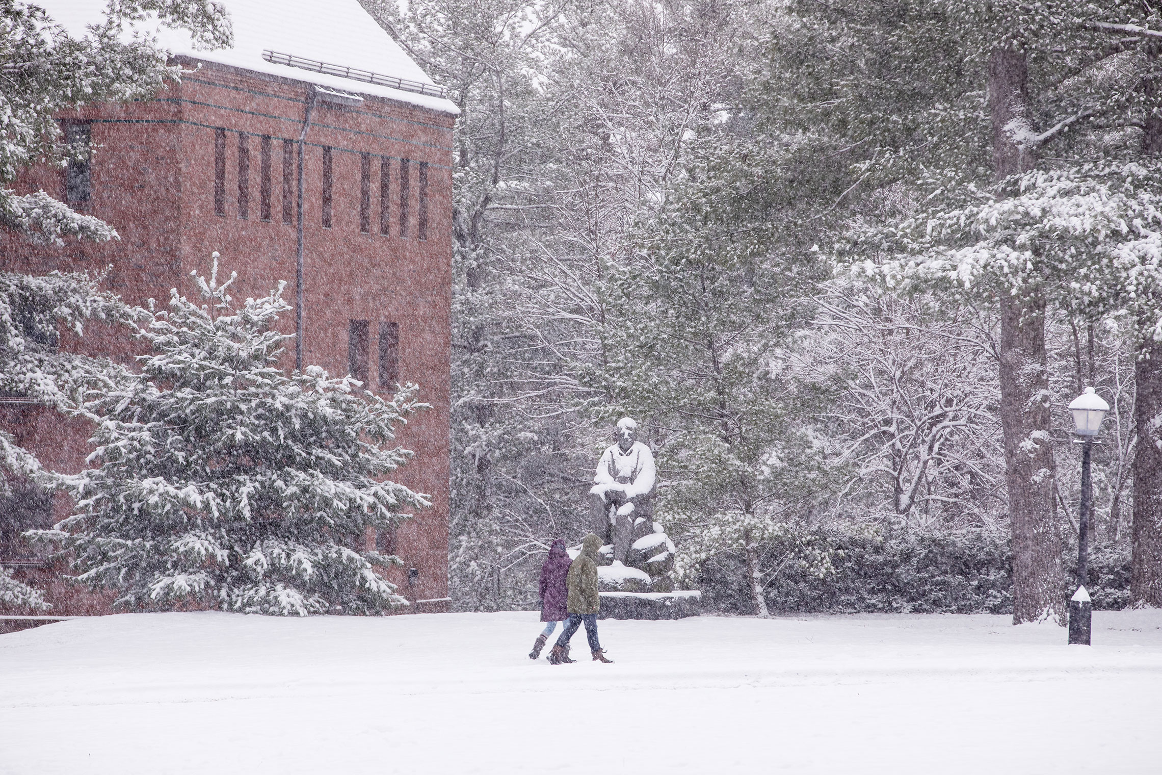 Students passing by a statue of Robert Frost on a snowy day.