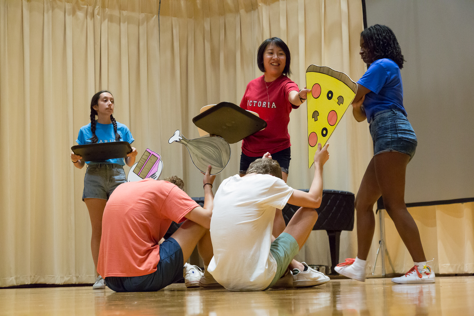 Students holding large cut outs of food perform a skit about healthy attitudes towards nutrition.