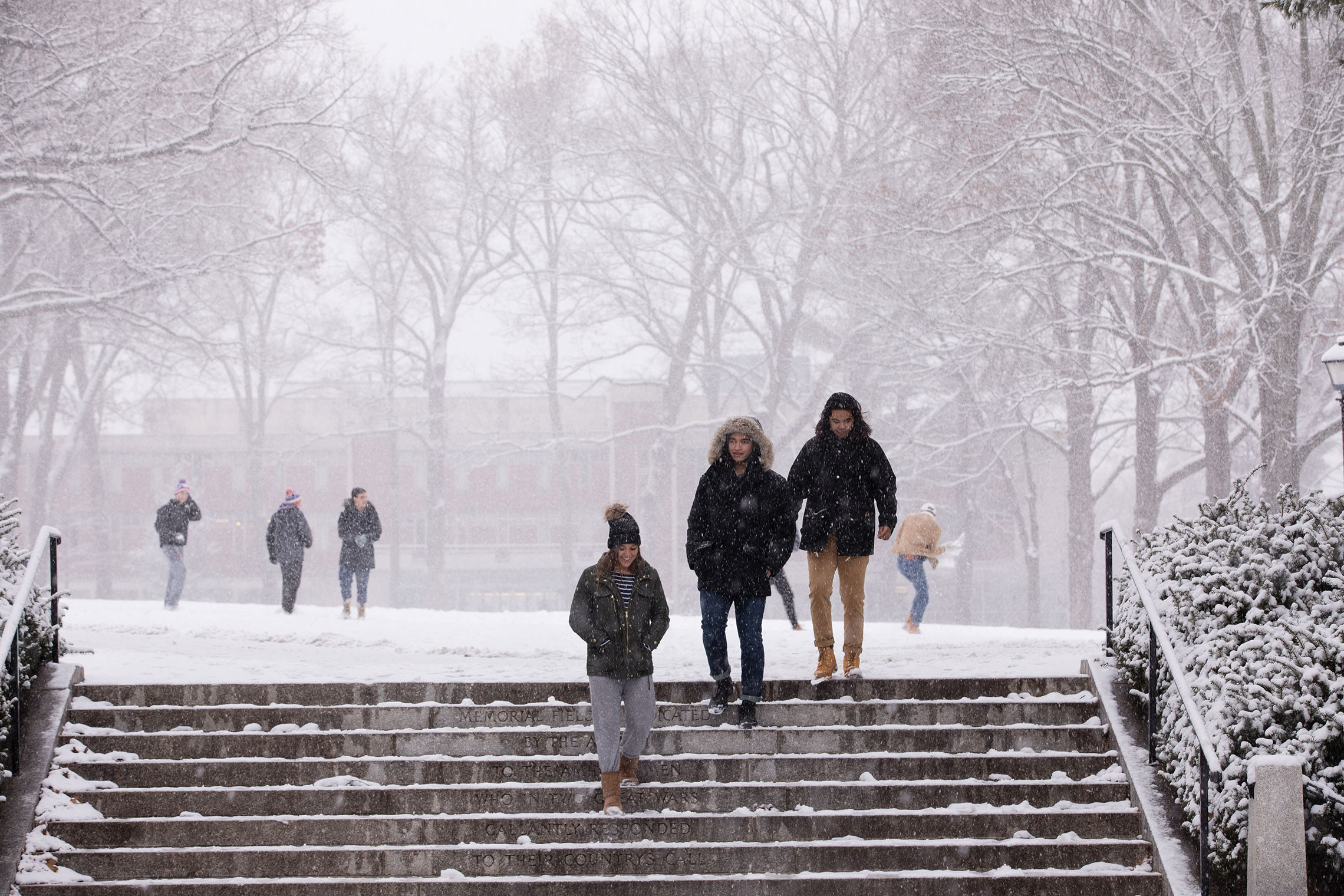 Student walking across campus during the first snowfall of 2017.