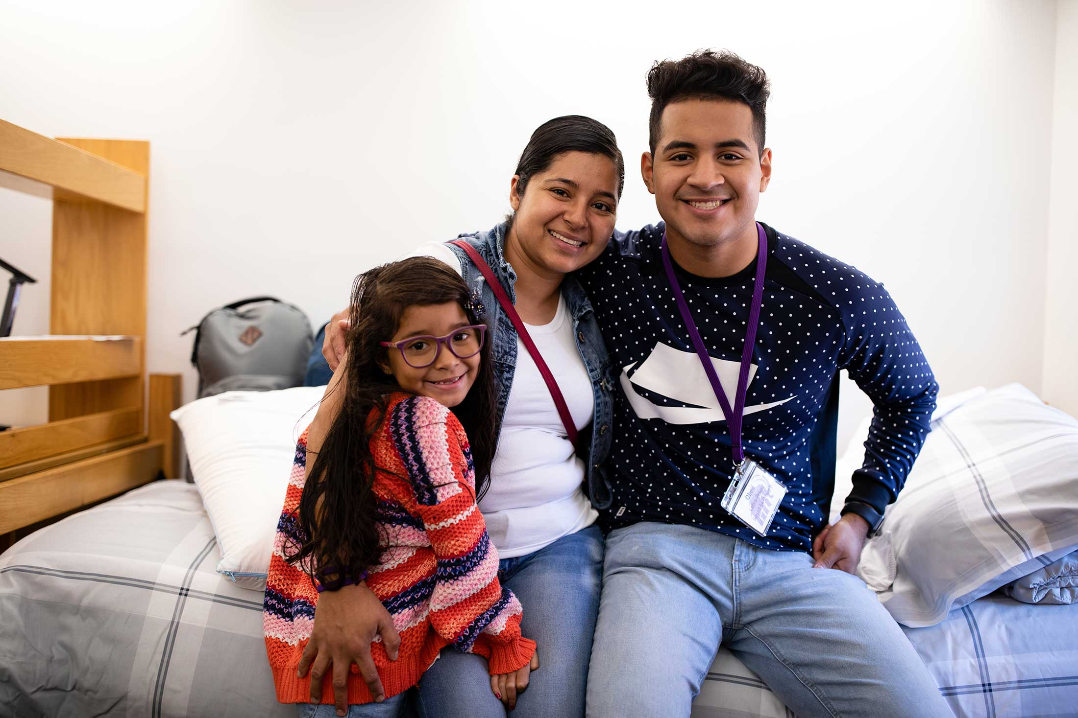 A first year student sitting on a bed in his new residence hall, with his arms around his mother and little sister