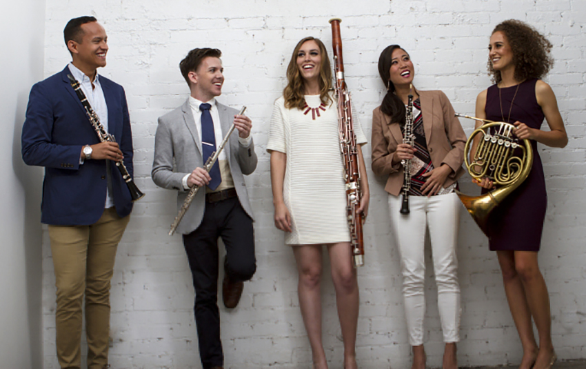 Portrait of Windsync holding their instruments, standing in a line