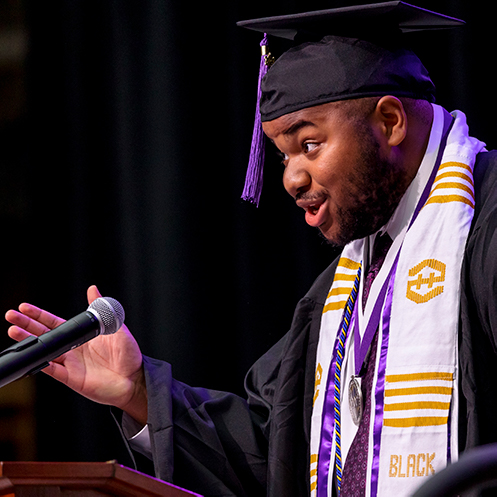 A student wearing commencement regalia at a podium speaking into a microphone