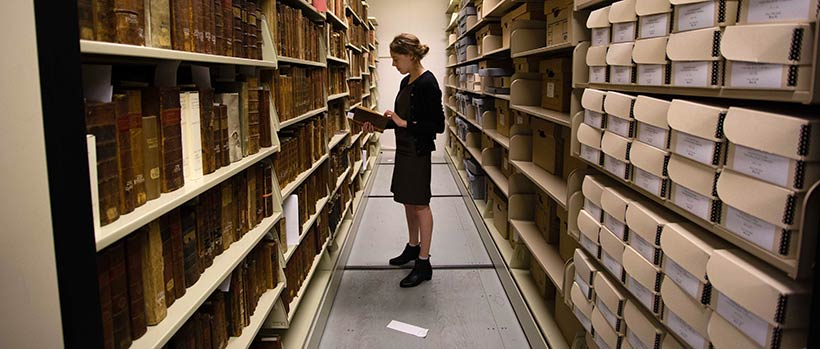 Emma Hartman '17 stands in the stacks.