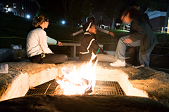 Three students sitting in front of a fire pit at night