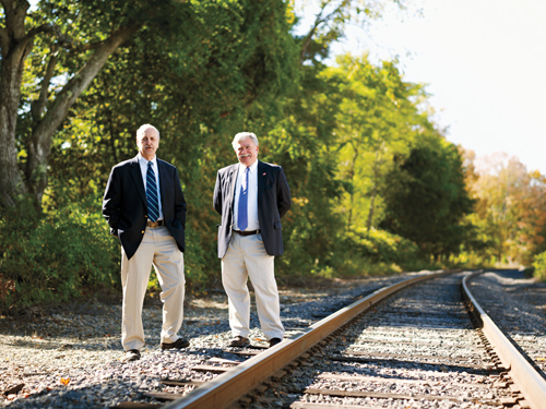 George Betke '59 and Mike Smith '68 standing beside railroad tracks