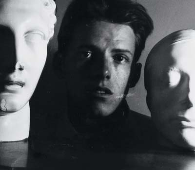 James Merrill '47 posed between a scultpure of a Hermes and a life mask of Keats.