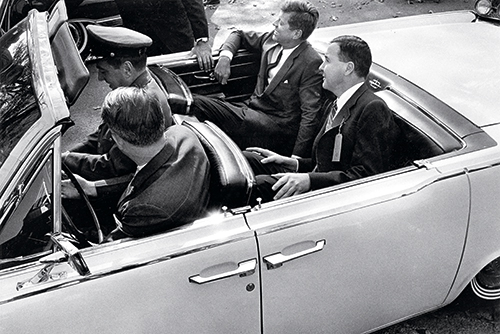 Kennedy riding in a motorcade along South Pleasant Street with Amherst President Calvin Plimpton '39