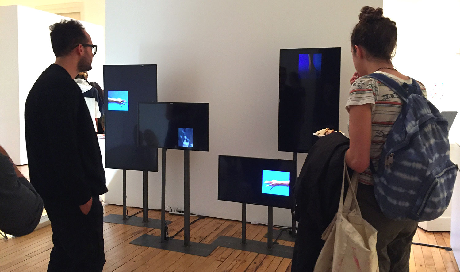 Installation view of TV monitors and two people looking at them