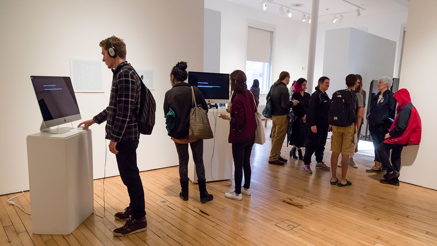 Gallery goers mingle around pedestals with TVs set up on top