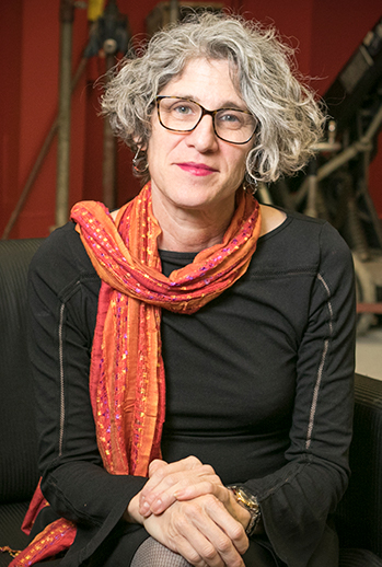 A woman with gray hair, glasses and a scarf