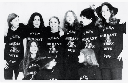 """Faculty women in 1974 wearing """"Keep Abreast of the Times"""" T-shirts"""
