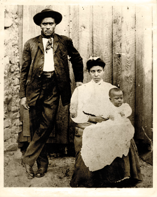 Ned Cobb posed by wood door, with wife Viola and son Andrew
