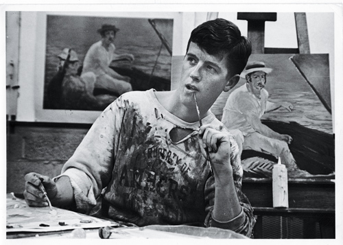 Student with paint on shirt in front of canvas