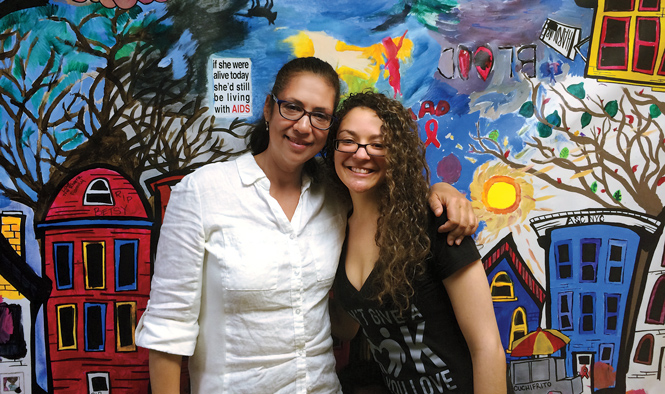 Susan and Christina Rodriquez pose in front of painted mural.