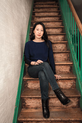 Deanna Fei '99 sitting on stairway in her home