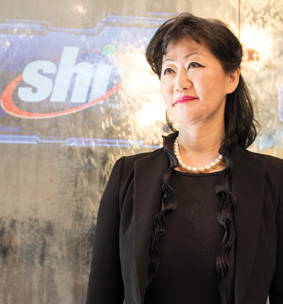 Thai Lee '80 standing by SHI sign