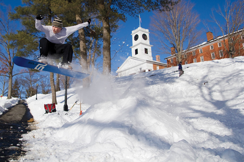 Student snowboarder airborne in front of Johnson Chapel