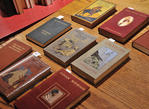Eight books arrayed on table in library