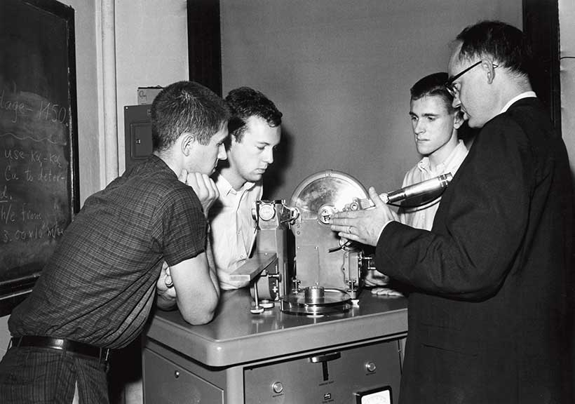 Professor Bruce B. Benson and three '64 physics majors check out a powder camera mounted on an x-ray generator
