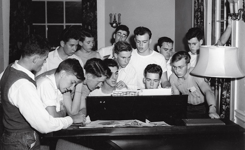 Members of  Phi Alpha Psi gathered around a piano singing
