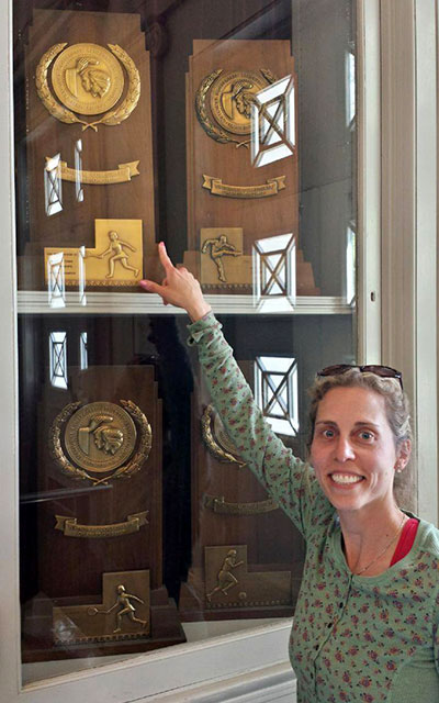 A woman points at a trophy in  a case