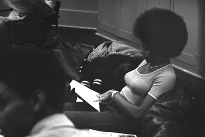a Black woman reading, on the Amherst campus in the 1970s