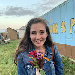 Bella holding a bunch of flowers on Book and Plow farm