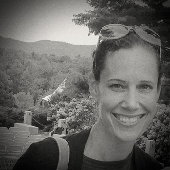 A black and white photo of a woman smiling with a forest in the background
