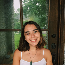 Bianca smilling widely in front of a window