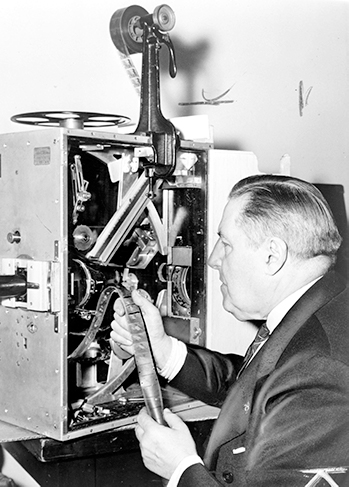 A black and white photo of a man inspecting film coming out of a projector