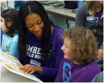 Student-athlete Camille Youngblood '15 reads to a girl as part of the Athletes Loves to Read initiative