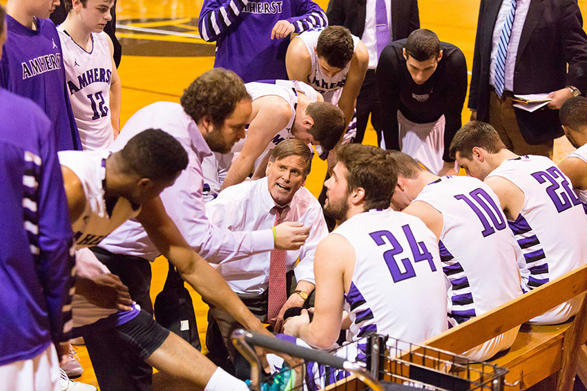 Coach Dave Hixon in a huddle with members of the men's basketball team