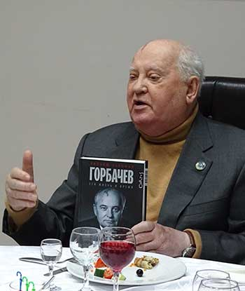 Mikhail Gorbachev holding a copy of William Taubman's biography of him
