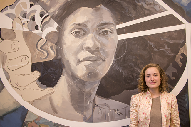 María Darrow standing in front of the mural, with Yenifer's face and outreached hand just behind her