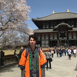 Dean standing in front of a temple and cherry blossoms