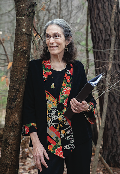 A photo of a woman in the woods holding a book