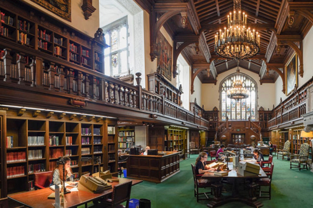 An ornate library with wood beamed ceilings and bookcases