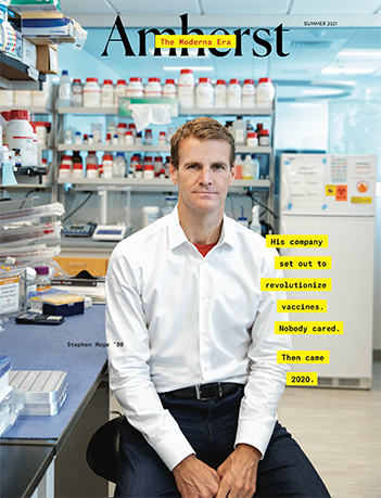 The front cover of the summer 2021 Amherst Magazine with a man in a white shirt sitting in a lab