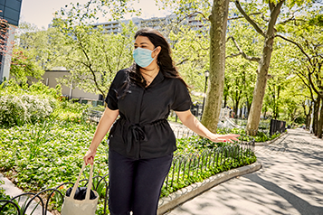 A woman in a face mask wearing a black medical uniform in a city park