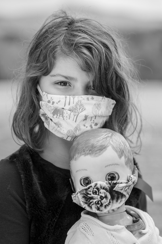 young Avelynn Augustin wears a mask while holding a doll wearing a mask