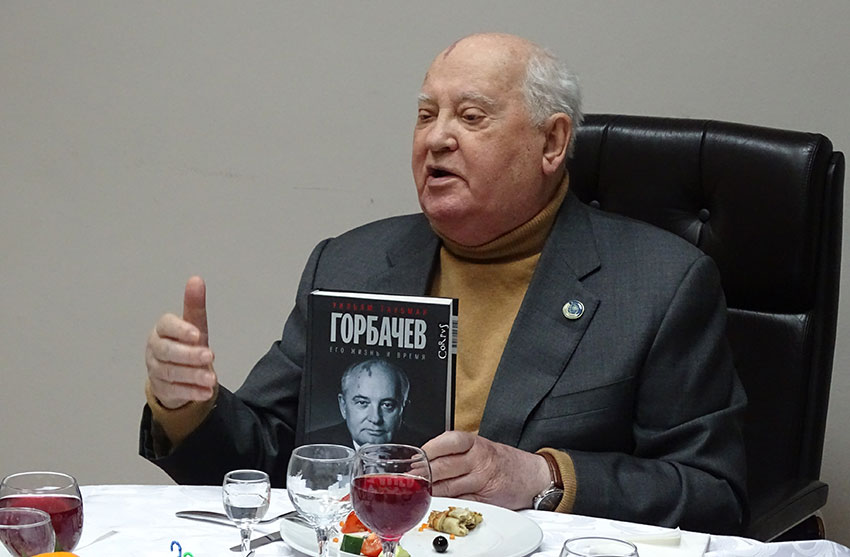 Mikhail Gorbachev holding a copy of William Taubman's biography of Gorbachev