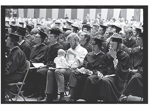 A black and white photo of a graduation crowd with a man holding a baby in his lap