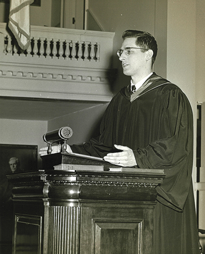 An old black and white photo of a young man speaking at a podium