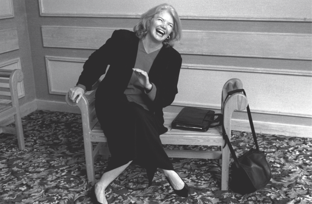 A black and white photo of a woman sitting and laughing